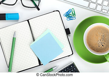 Green coffee cup and office supplies View from above Closeup...