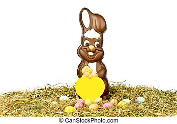 Easter bunny with colored eggs in straw and a yellow paper...