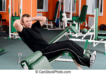 The man on training apparatus in sports club