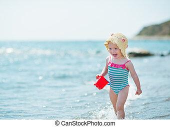 Happy baby running along sea shore