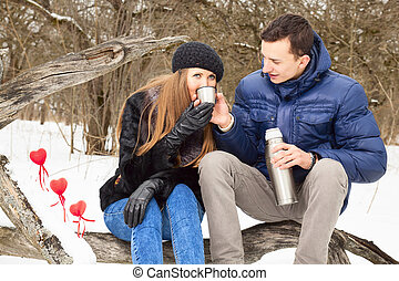 Beautiful adult couple in forest sitting an drinking tea