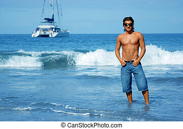 Young man and the ocean - Young man standing on the beach