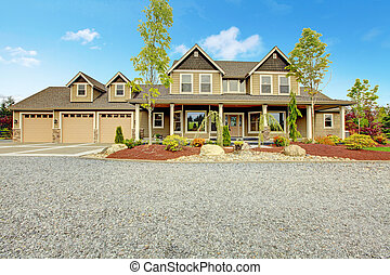 Large farm country house with gravel driveway and green...