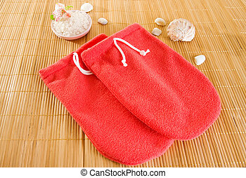 Red microfiber spa mitten and a salt on bamboo mat