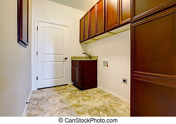New empty laundry room with wood cabinets.