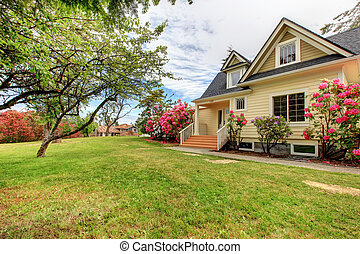 Yellow house exterior with spring blooming rhododendron