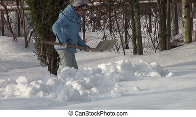 The girl with a shovel removes snow