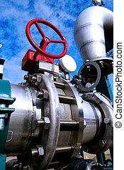 Industrial zone, Steel pipelines and valves against blue sky...