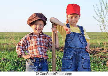 Two kids with shovel in the field - Two kids standing in...