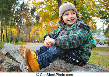 Beautiful boy in the autumn park - Beautiful boy sitting on...