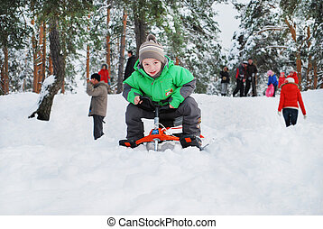Winter fun - Boy riding a snow-cats from the mountain in a...