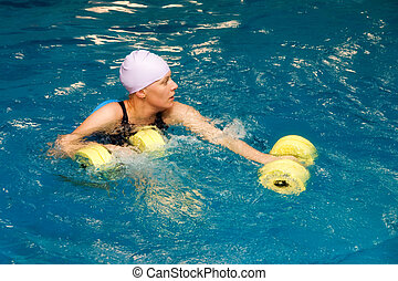 Girl in water with dumbbels - The girl is engaged aqua...