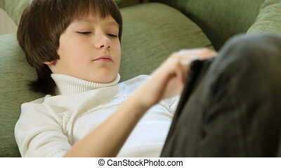 Child Using a Touch Screen Tablet - Teen Boy Using a Touch...