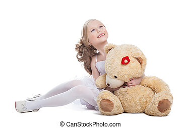 Beautiful little girl hugging big teddy bear, isolated on...