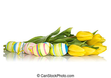 Yellow tulips and Easter eggs on the white background