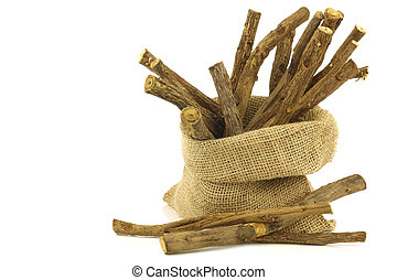 licorice root sticks in a burlap bag on white background