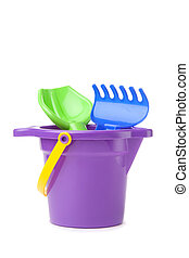 toy purple bucket with spade and rake over white background