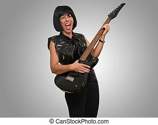Portrait Of Female Rockstar against a grey background