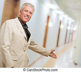 Portrait Of Man Doing A Welcome Gesture, indoor