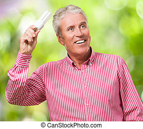 Happy Mature Man Holding Bulb Light against a nature...