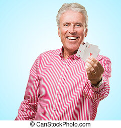 Happy Mature Man Holding Playing Cards against a blue...