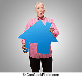 Happy Mature Man Holding House Model against a grey...