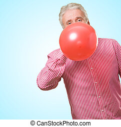 Mature Man Blowing Balloon against a blue background