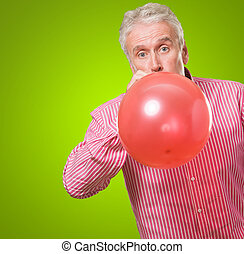 Handsome Man Blowing Balloon against a green background