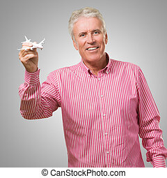 Happy Mature Man Holding Miniature Airplane against a grey...
