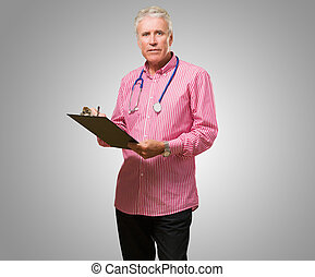 Male Doctor Holding Writing Pad against a grey background