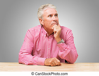 Portrait Of A Mature Man Thinking against a grey background