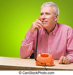 Handsome man talking on telephone against a green background