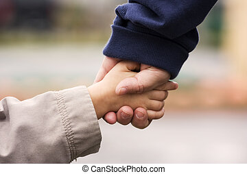 Hand in Hand - A grand-mother holding her grand-son\\\'s...