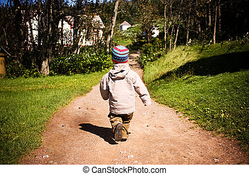 A little boy walking on a trail in wood