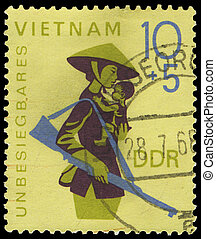 GDR - CIRCA 1968: A stamp printed in GDR, show theVietnam   woman with a gun and the child on hands, circa 1968