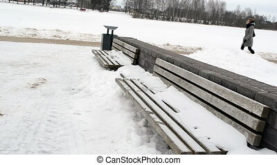 bench snow woman park - wooden bench covered with snow and...