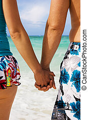 Holding hands - A young couple holding hands on the beach in...