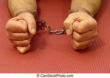 handcuffed man - handcuffs on a prisoners wrist over a...