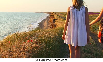 On a sunny day - Two women walking along the coast on a...
