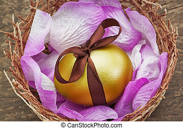 Easter golden egg with brown ribbon in a nest on a wooden...