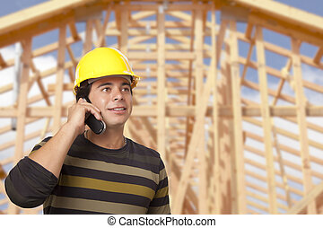 Hispanic Male Contractor on Phone in Front of House Framing