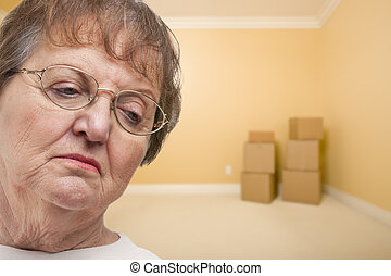 Sad Older Woman In Empty Room with Boxes - Concept for...
