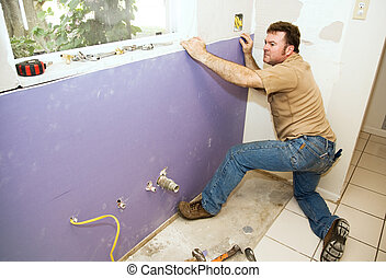 Worker Installing Drywall - Contractor installing a large...