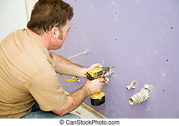 Carpenter Installs Drywall - Carpenter using a power drill...