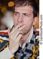 man smokes a cigarette against a dark background - The man...