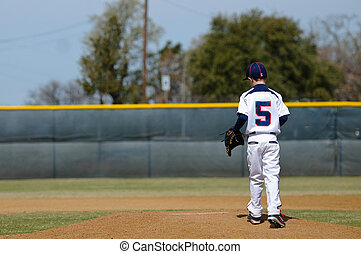 Little league baseball player taking the mound to pitch.