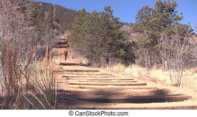 Woman jogging down Manitou Incline in Colorado in athletic...