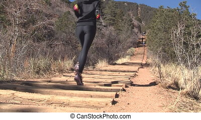 Woman running up Manitou Incline in Colorado in athletic...