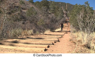 Woman walking down Manitou Incline in Colorado in athletic...