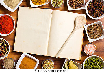 Cookbook and various spices and herbs. - The cookbook and...